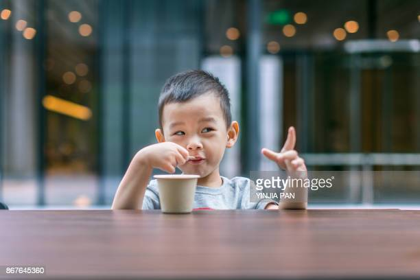Portrait of baby boy eating ice cream with smile