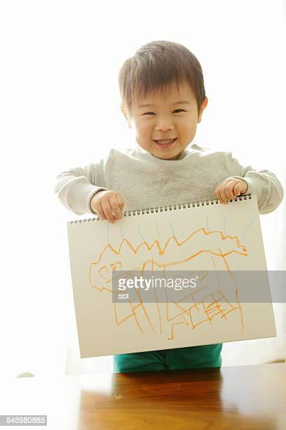 Portrait of baby boy having sketchbook
