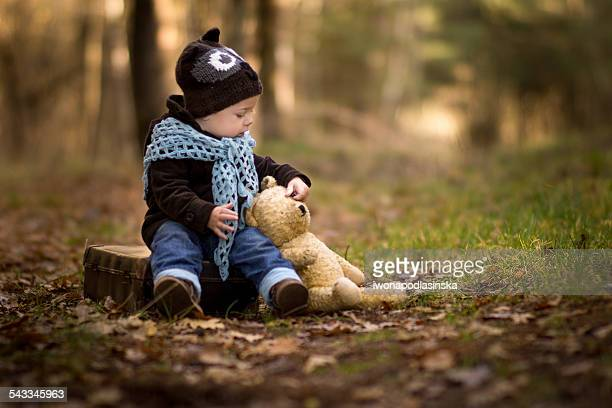 Portrait of baby boy sitting in forest with his teddy bear