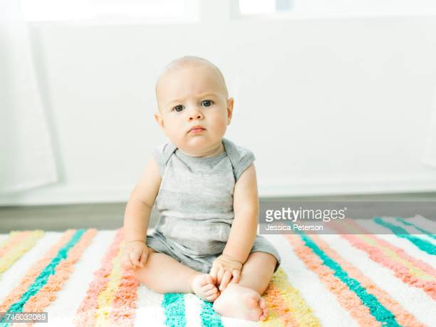 Portrait of baby boy (6-11 months) sitting on colorful carpet