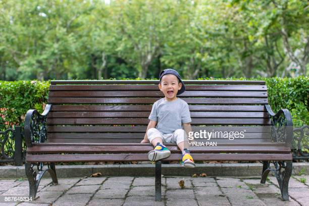 Portrait of baby boy sitting on the bench with laugh