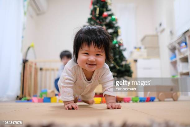 portrait of baby crawling floor at christmas - one baby girl only stock pictures, royalty-free photos & images