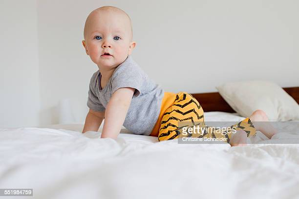 Portrait of baby girl crawling on bed