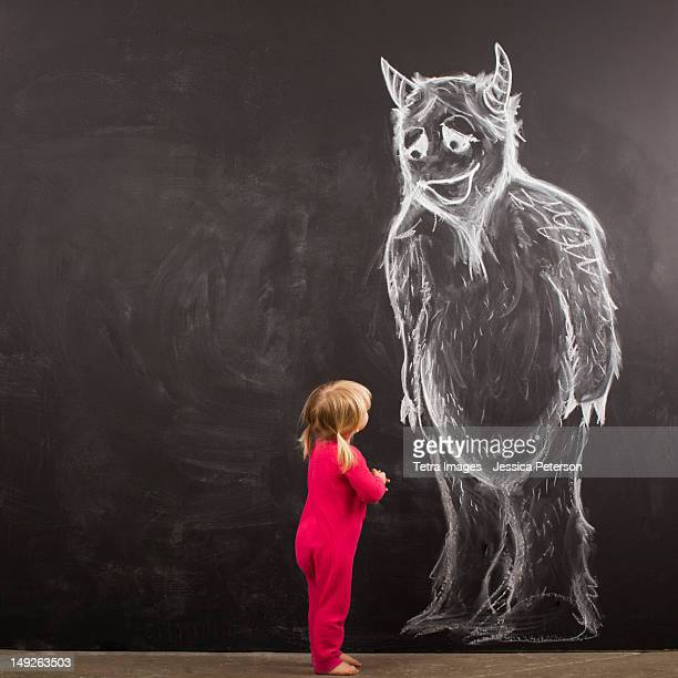 Portrait of baby girl (18-23 months) in front of huge monster drawn on blackboard