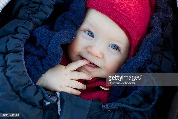 Portrait of baby girl in sleeping bag wearing hat