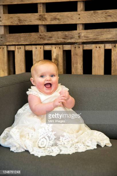 portrait of baby girl in white gown during naming ceremony in an historic barn. - white dress stock pictures, royalty-free photos & images