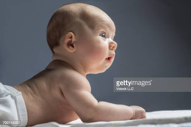 portrait of baby girl (6-11 months) lying down on bed - 6 11 months stock pictures, royalty-free photos & images