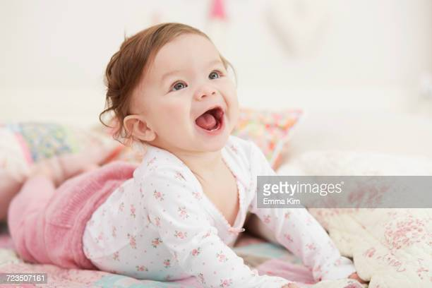 portrait of baby girl, lying on her front, laughing - baby girls stock photos and pictures
