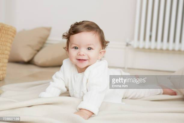 Portrait of baby girl lying on her front, smiling