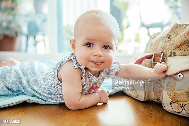 Portrait of baby girl lying on the floor grabbing bag