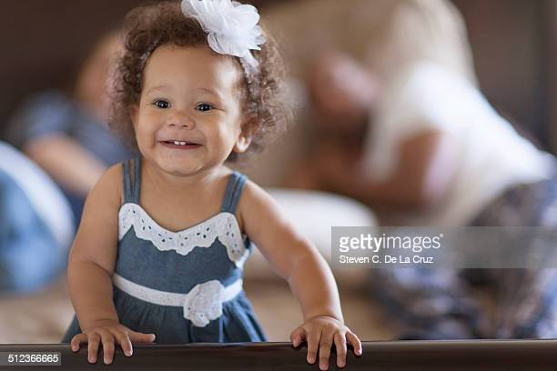 Portrait of baby girl, parents behind