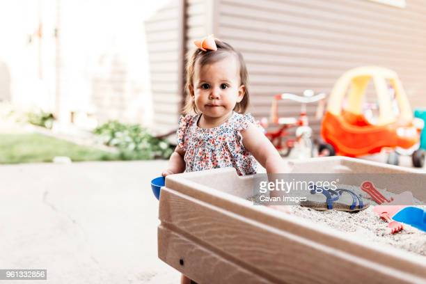 Portrait of baby girl playing with sand in backyard