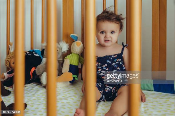 Portrait of baby girl sitting in bed