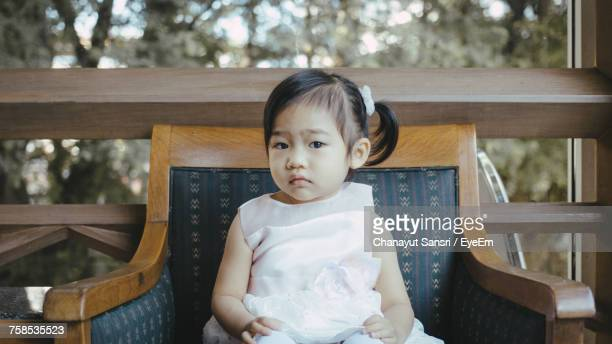 portrait of baby girl sitting on armchair - chanayut stock photos and pictures