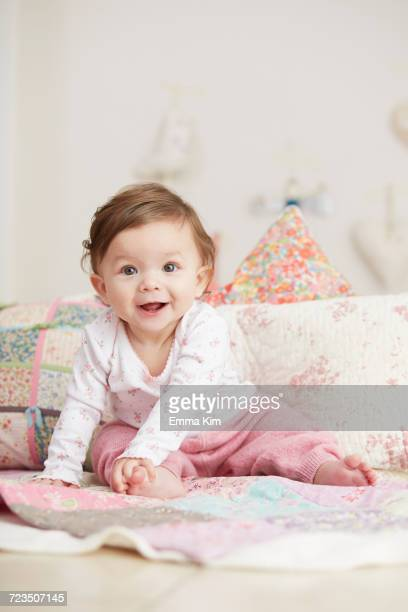 Portrait of baby girl, sitting on blanket, laughing