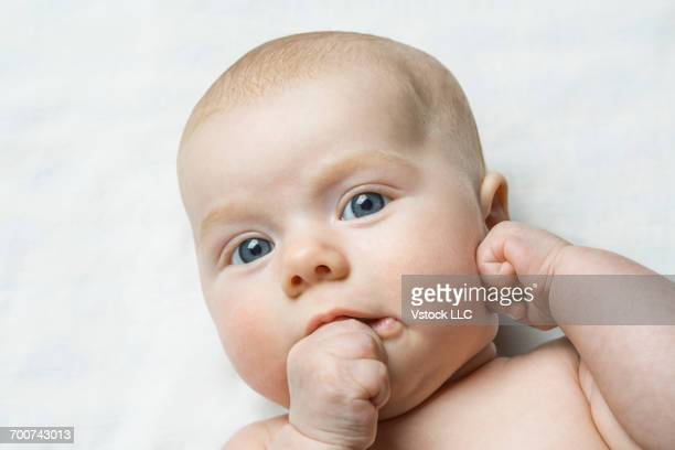 portrait of baby girl (6-11 months) sucking thumb - 6 11 months stock pictures, royalty-free photos & images