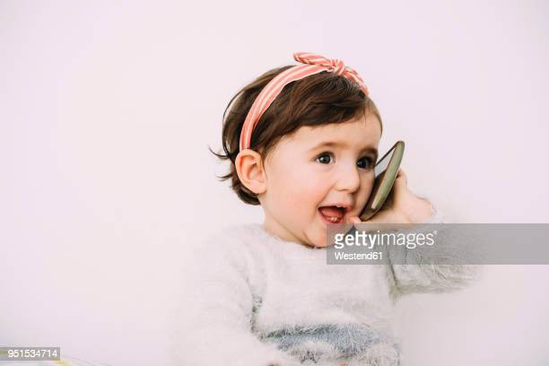 Portrait of baby girl using cell phone