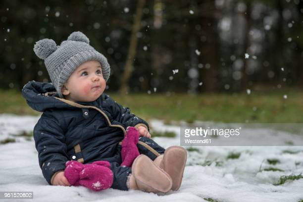 portrait of baby girl watching snowflakes for the first time - first occurrence stock pictures, royalty-free photos & images