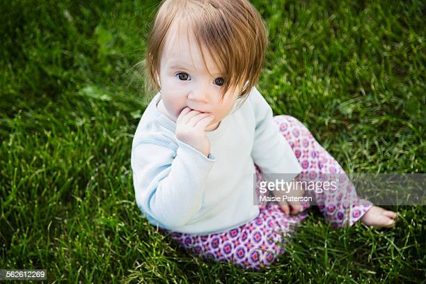 portrait of baby girl (6-11 months) with hand in mouth - 6 11 months stock pictures, royalty-free photos & images