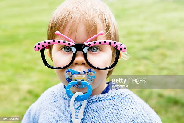 Portrait of baby girl with pacifier wearing fun butterfly glasses