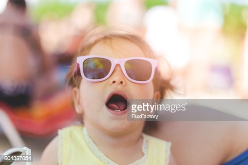 210023411da4 Portrait Of Baby Girl With Sunglasses On A Beach Stock Photo