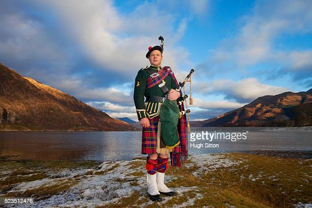 portrait of bagpiper standing next to loch etive, mountains in the background. west coast scotland - bagpipes stock pictures, royalty-free photos & images