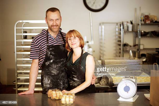 Portrait of baker couple behind kitchen counter