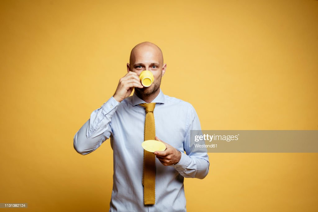 Portrait of bald businessman drinking cup of coffee against yellow background : Stock Photo