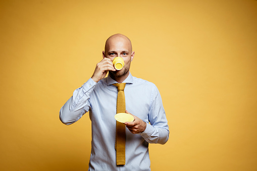 Portrait of bald businessman drinking cup of coffee against yellow background - gettyimageskorea