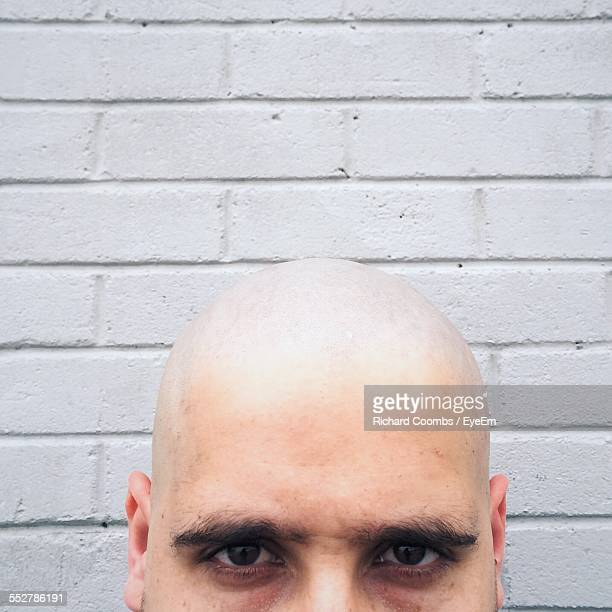 portrait of bald man against brick wall - completamente calvo foto e immagini stock