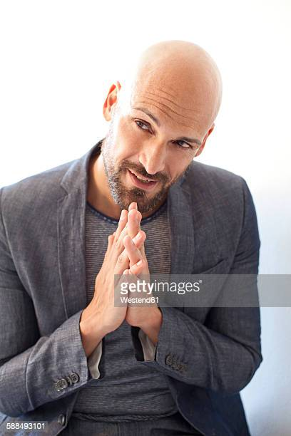 Portrait of bald man in grey suit asking for forgiveness