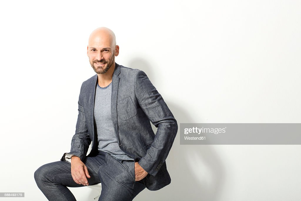 Portrait of bald man wearing grey suit sitting in front of white background : Foto de stock