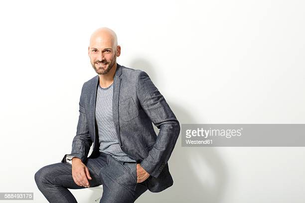 Portrait of bald man wearing grey suit sitting in front of white background