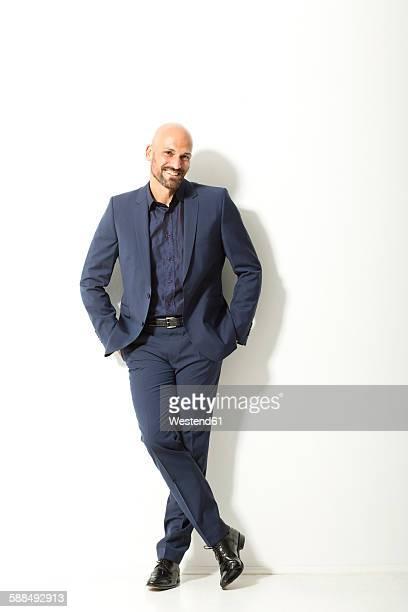 portrait of bald man with beard wearing blue suit in front of white background - handen in de zakken stockfoto's en -beelden