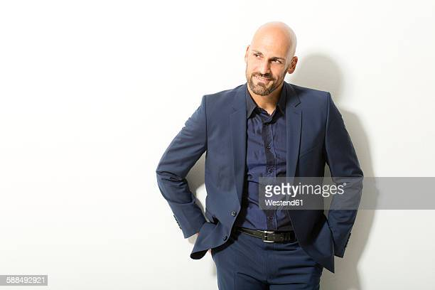portrait of bald man with beard wearing blue suit in front of white background - hair loss stock pictures, royalty-free photos & images