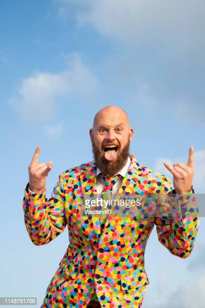portrait of bald man with beard  wearing suit with colourful polka-dots sticking out tongue - ugly bald man stock pictures, royalty-free photos & images