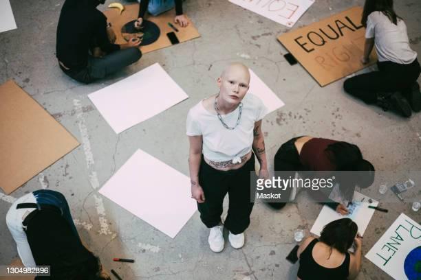 portrait of bald woman standing while female activists preparing signboards for social issues - soziale gerechtigkeit stock-fotos und bilder
