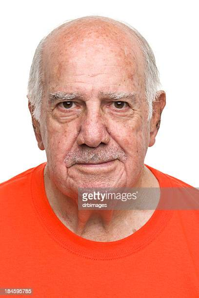 Portrait of balding grey haired man in orange crewneck