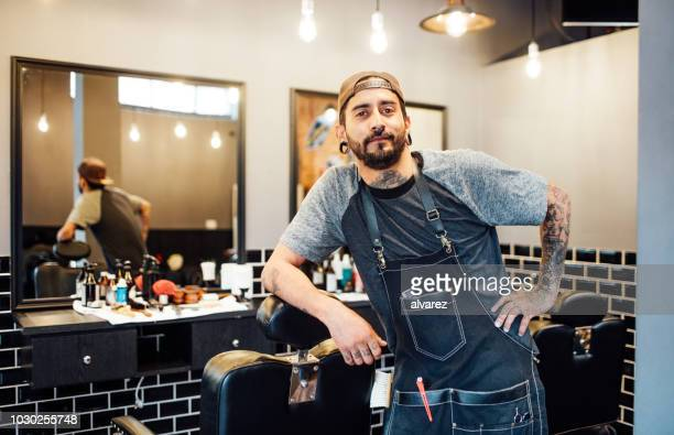 portrait of barber leaning on chair in salon - barber shop stock photos and pictures