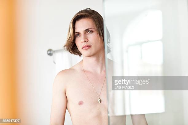 Portrait of bare chested young man in hotel bathroom