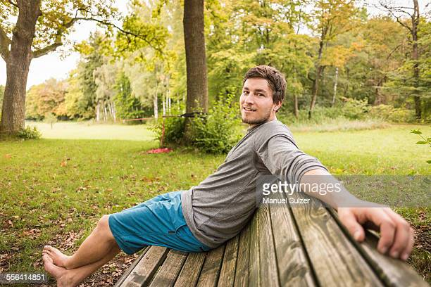 Portrait of barefoot young man sitting on park bench