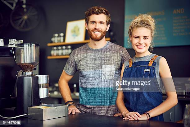 Portrait of baristas smiling at counter in cafe
