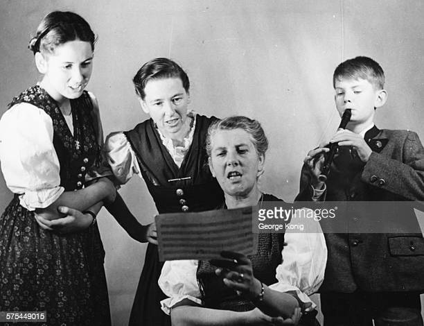 Portrait of Baroness Maria Von Trapp and three of her children Eleonore Agatha and Johannes singing from a piece of sheet music London circa 1950