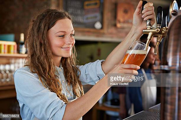 Portrait of bartender at microbrewery pouring beer