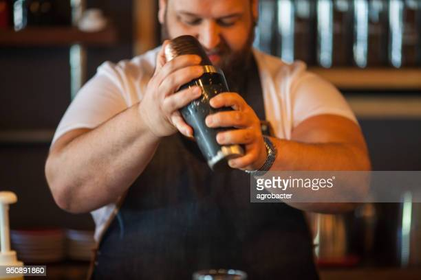 Portrait of bartender using cocktail shaker at bar