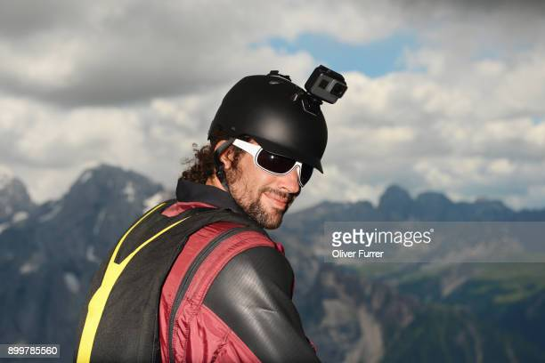 portrait of base jumper wearing wingsuit with action camera on helmet, dolomite mountains, canazei, trentino alto adige, italy, europe - sports helmet stock pictures, royalty-free photos & images
