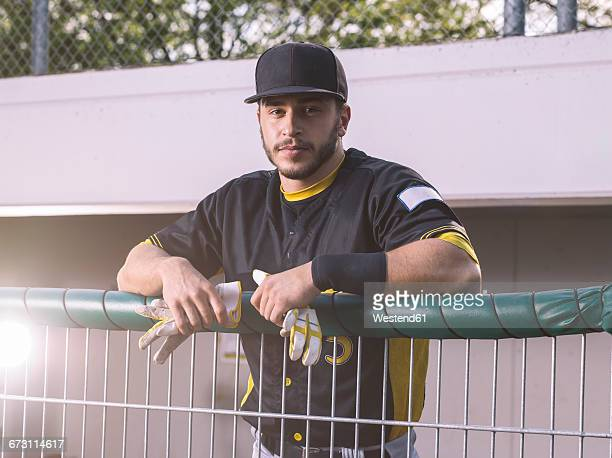 Portrait of baseball player behind fence