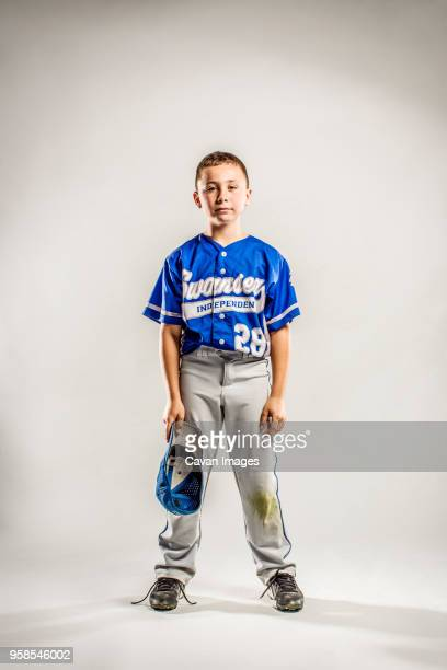 portrait of baseball player with cap in hand against white background - baseball player stock pictures, royalty-free photos & images