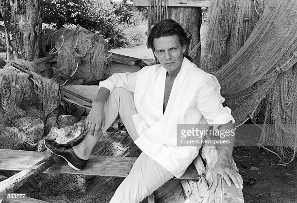 Portrait of bassist Andy Taylor of the British pop group Duran Duran posing in a dry docked fisherman's boat probably on location for a video shoot...