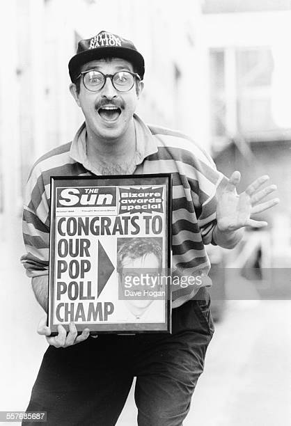 Portrait of BBC Radio 1 disc jockey Steve Wright posing with a copy of 'The Sun' newspaper which features him on the front page circa 1987